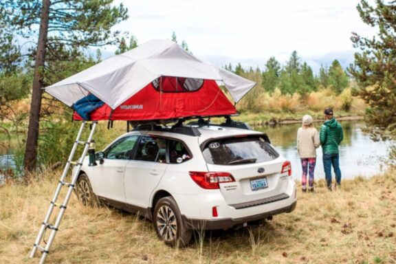 Yakima roof top tent set up on a Subaru with the ladder extending down to the ground with a couple looking at a lake and nature behind the vehicle.