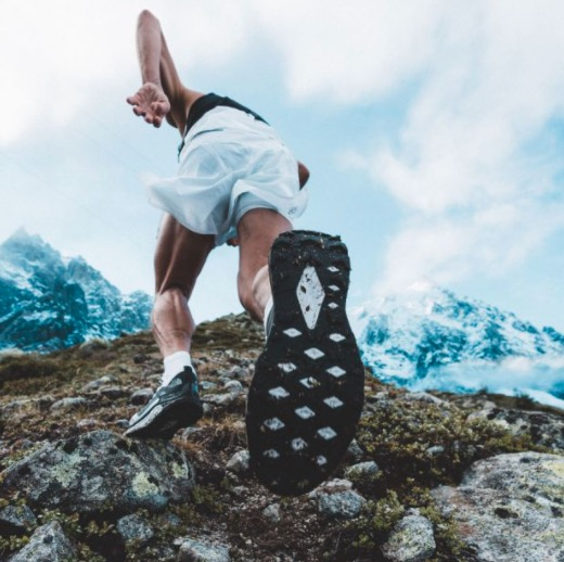 This is a picture of a male runner in mi-stride up a rocky trail wearing The North Face Vectiv running shoes. The bottom sole of the shoe is also visible as the image is from a low angle.
