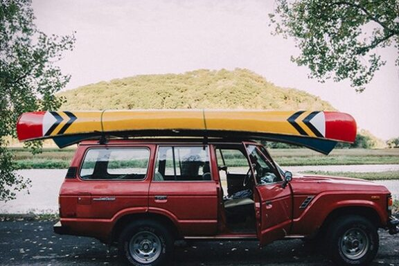 This image shows the Sanborn Prospector Canoe mounted on top of red Land Crusier FJ60. The Sanborn Canoe is yelloe with red and white and black accents.