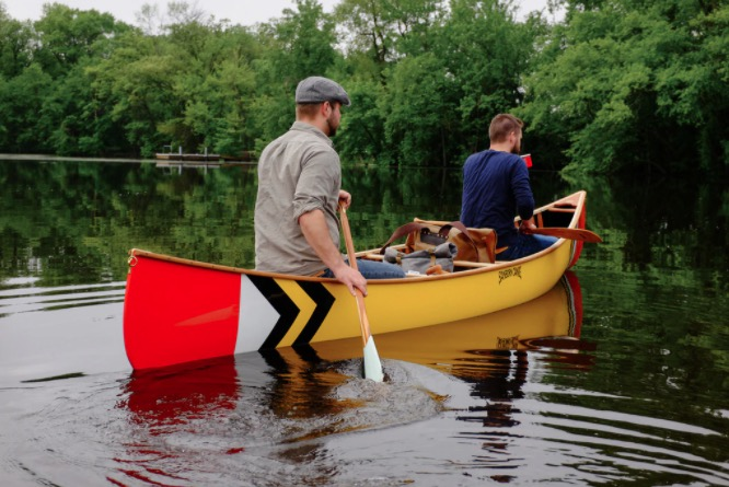 This image shows the Sanborn Prospector Canoe in calm lake or river water with two paddlers sitting in it holding Sanborn Paddles.